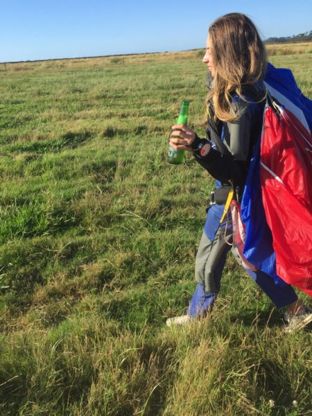Luci Martyn walking in from a skydive with an Icarus canopy and a beer