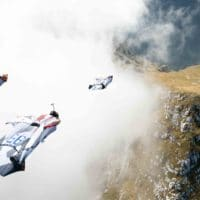 Wingsuit BASE in mountains through cloud photo by Scott Patterson original photo on Icarus skydiving photography blog