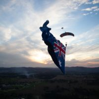 Skydiver under canopy with a flying flag