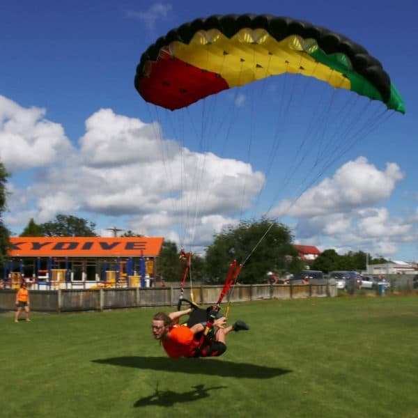 skydiver swooping Leia close to ground fully extended out of harness