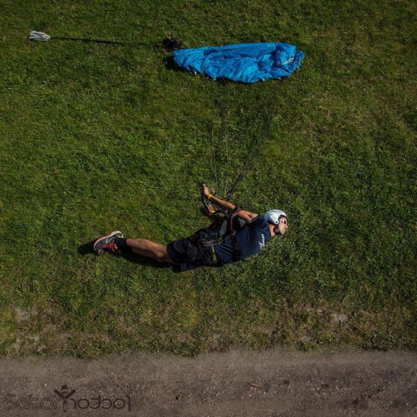 skydiver lying in swooping position on grass with canopy laid out as if flying through air
